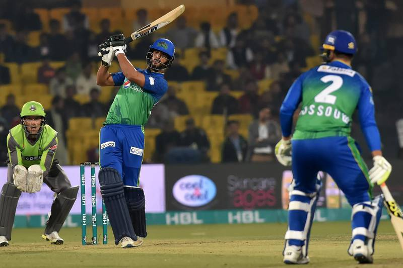Multan Sultans's Shan Masood (2L) hits a shot as Lahore Qalandars's wicketkeeper Dane Vilas (L) looks on during the Pakistan Super League (PSL) Twenty20 cricket match between Multan Sultans and Lahore Qalandars at The Gaddafi Cricket Stadium in Lahore on February 21, 2020. (Photo by Arif ALI / AFP)