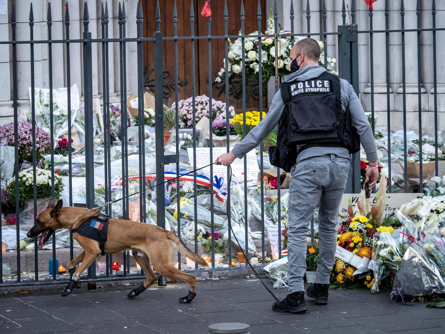 """NICE, FRANCE - NOVEMBER 01: A police officer with a sniffer dog checks flowers in front of Notre Dame basilica, before a mass to pay tribute to the victims on November 01, 2020 in Nice, France. A 21-year-old Tunisian man is accused of fatally stabbing three people in the church on Thursday, in what French President Emmanuel Macron described as an """"Islamist terrorist attack."""" The attacker was shot and wounded by police and is reported to be in critical condition. (Photo by Arnold Jerocki/Getty Images)"""