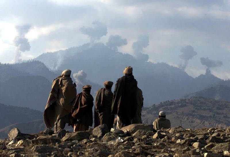 Anti-Taliban Afghan fighters watch several explosions from U.S. bombings in the Tora Bora mountains in Afghanistan December 16, 2001. [Hundreds of al Qaeda fighters have battled to the death in a last stand in eastern Afghanistan, but their leader Osama bin Laden eluded the U.S. dragnet, Afghan commanders said on Sunday.]