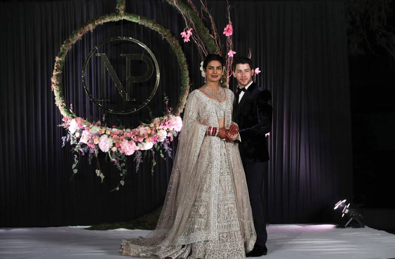epa07208514 Newlyweds, Bollywood actress Priyanka Chopra (L) and US musician Nick Jonas (R) pose for photographs during a reception in New Delhi, India, 04 December 2018. According to media reports, the couple hosted wedding celebrations in Jodphur on 01 and 02 December.  EPA-EFE/RAJAT GUPTA