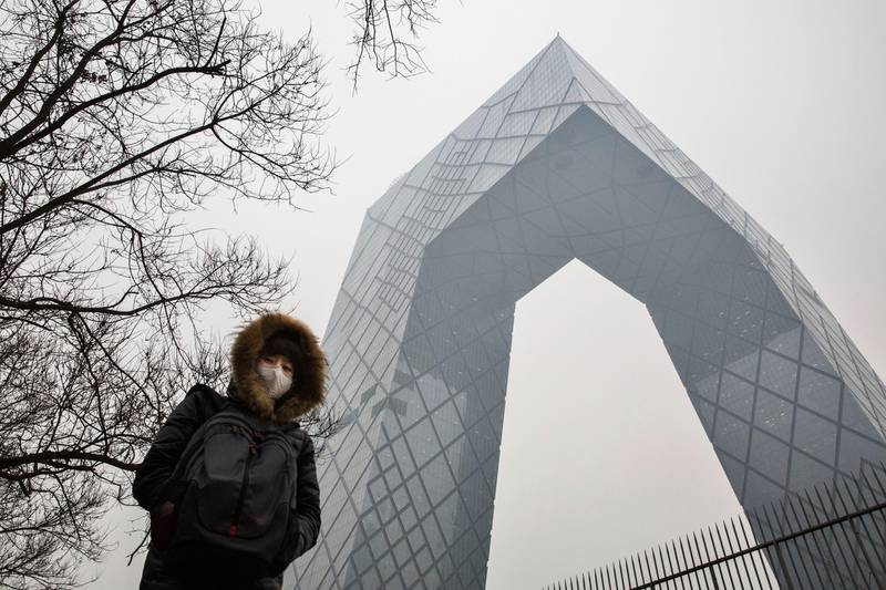 """BEIJING, CHINA - DECEMBER 08:  A Chinese woman wears a mask to protect against pollution as she passes the CCTV building in heavy smog on December 8, 2015 in Beijing, China. The Beijing government issued a """"red alert"""" for the first time since new standards were introduced earlier this year as the city and many parts of northern China were shrouded in heavy pollution. Levels of PM 2.5, considered the most hazardous, crossed 400 units in Beijing, lower than last week, but still nearly 20 times the acceptable standard set by the World Health Organization. The governments of more than 190 countries are meeting in Paris to set targets on reducing carbon emissions in an attempt to forge a new global agreement on climate change.  (Photo by Kevin Frayer/Getty Images)"""