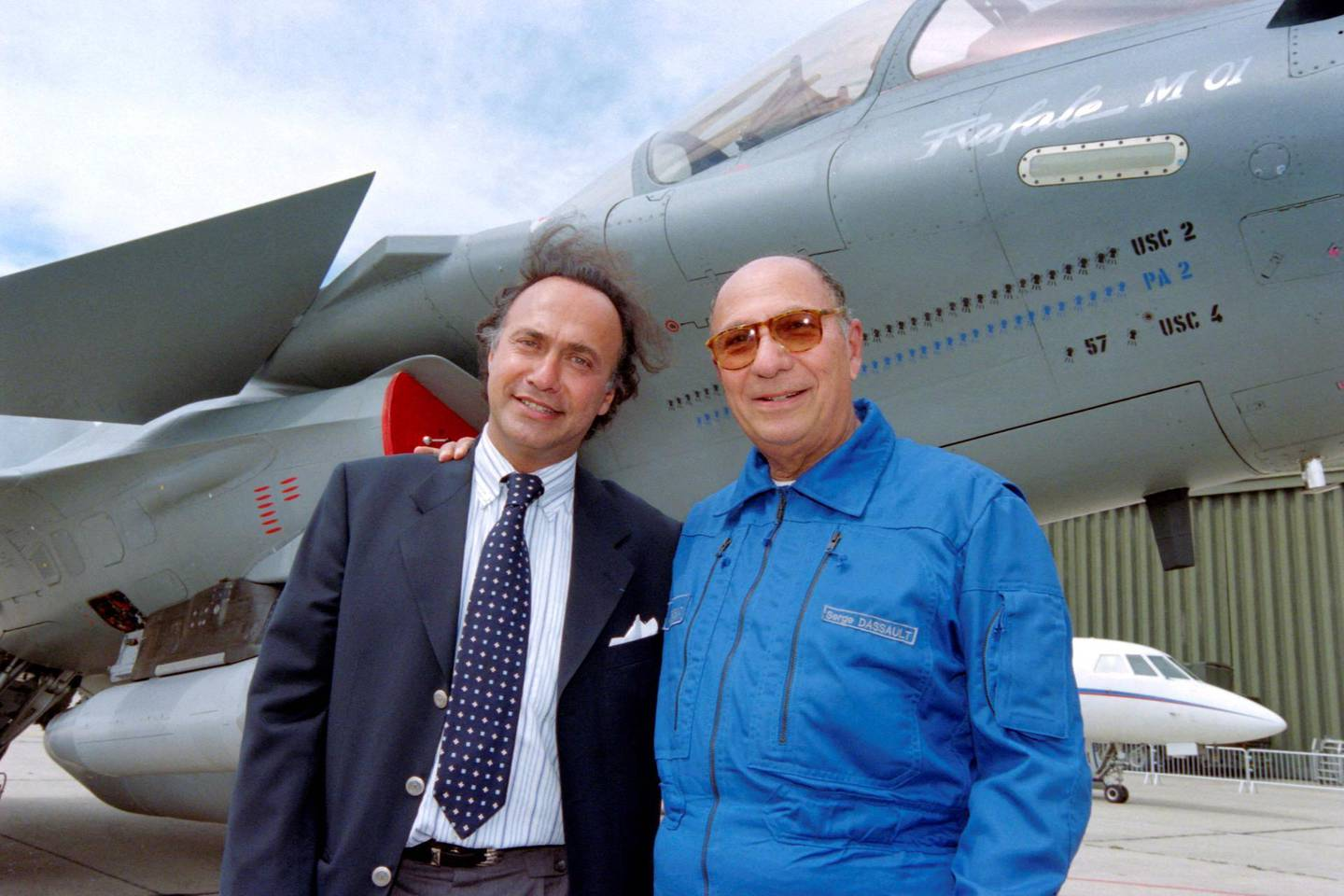 (FILES) In this file photo taken on June 11, 1997 Serge Dassault (R), Dassault Group CEO, poses with his son Olivier Dassault in front of a Rafale M01 jet fighter in Le Bourget, near Paris.  Olivier Dassault has died in the crash of his helicopter near Deauville, a parlamentiary source said on March 7, 2021. / AFP / Jack GUEZ
