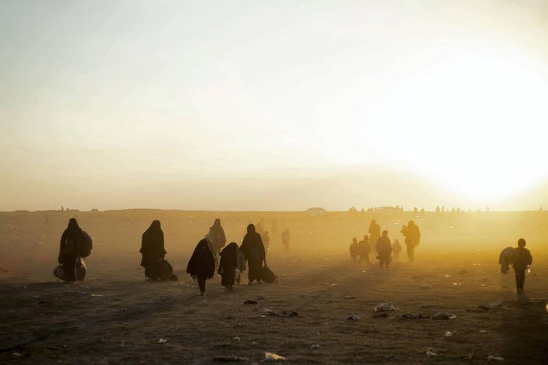 Women and children evacuated from the Islamic State (IS) group's embattled holdout of Baghouz arrive at a screening area held by the US-backed Kurdish-led Syrian Democratic Forces (SDF), in the eastern Syrian province of Deir Ezzor, on March 6, 2019. - Veiled women carrying babies and wounded men on crutches hobbled out of the last jihadist village in eastern Syria on March 6 after US-backed forces pummelled the besieged enclave. The Syrian Democratic Forces leading the assault expected more fighters to surrender with their families in tow before moving deeper in the Islamic State group's last redoubt. (Photo by Delil souleiman / AFP)