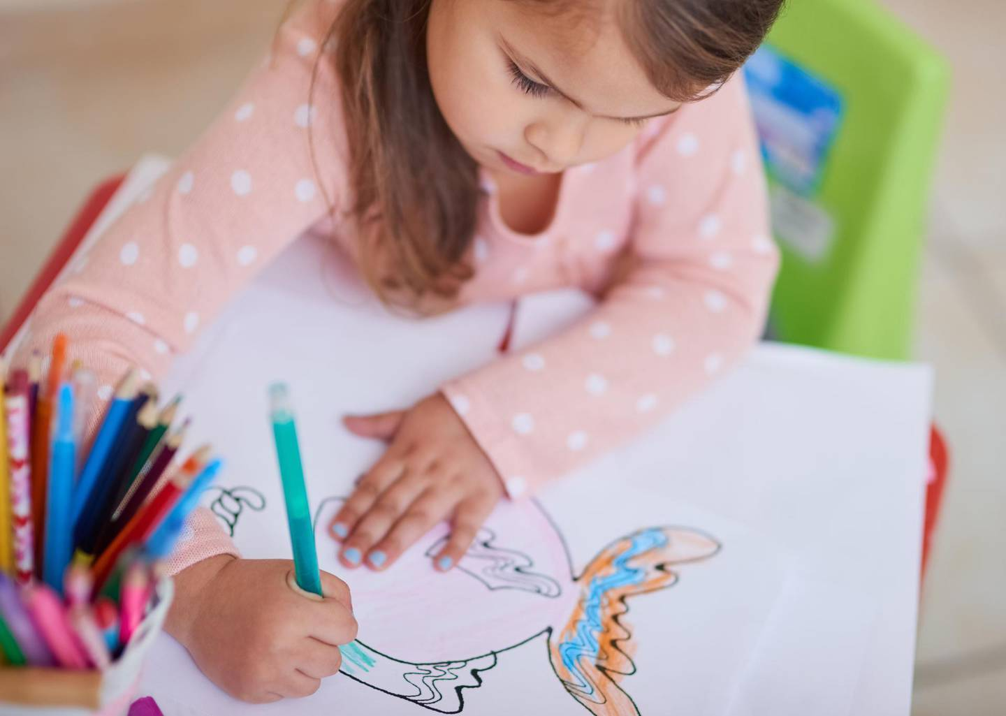 High angle shot of a little girl colouring in a picture at home. Getty Images
