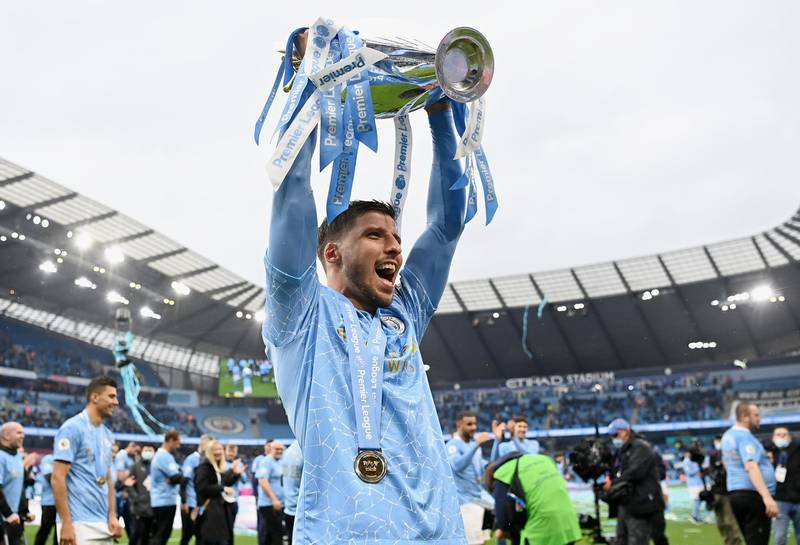 MANCHESTER, ENGLAND - MAY 23: Ruben Dias of Manchester City celebrates with the Premier League Trophy as Manchester City are presented with the Trophy as they win the league following the Premier League match between Manchester City and Everton at Etihad Stadium on May 23, 2021 in Manchester, England. A limited number of fans will be allowed into Premier League stadiums as Coronavirus restrictions begin to ease in the UK. (Photo by Michael Regan/Getty Images)