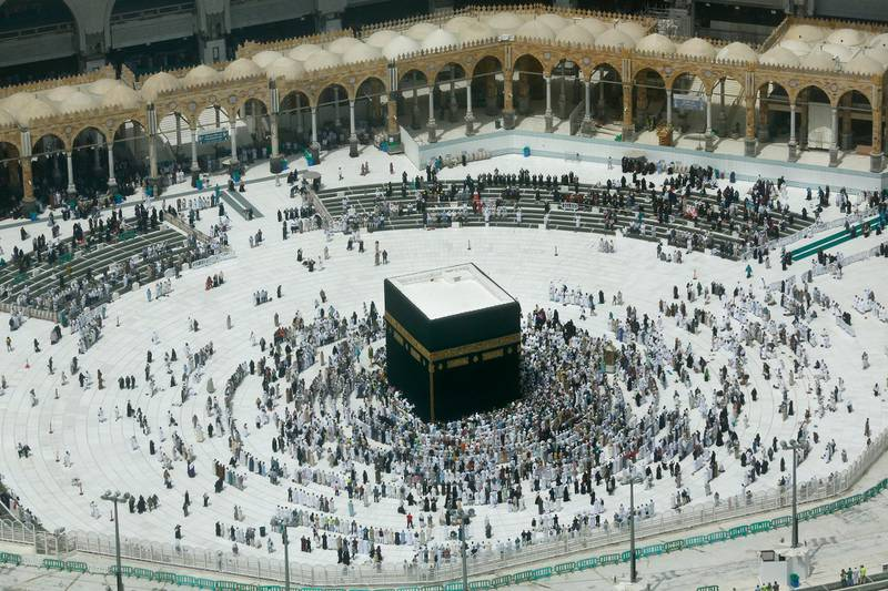 A relatively few number of Muslims pray around the Kaaba, the cubic building at the Grand Mosque, in the Muslim holy city of Mecca, Saudi Arabia, Wednesday, March 4, 2020. On Wednesday, Saudi Arabia's Deputy Health Minister Abdel-Fattah Mashat was quoted on the state-linked news site Al-Yaum saying that groups of visitors to Mecca from inside the country would now also be barred from performing the pilgrimage, known as the umrah. (AP Photo/Amr Nabil)