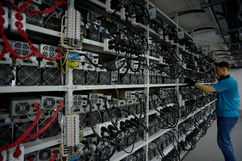 """An employee inspects machines for the production of bitcoins and lightcoins at the """"CryptoJuniversóe"""" mining centre during a presentation of the centre for the crypto currency in Kirishi on August 20, 2018. - A Russian company opened on August 20, 2018 what it said was the country's largest cryptocurrency mining unit, in a former Soviet fertilizer-producing laboratory. The opening comes as Russian authorities seek to regulate the booming cryptocurrency sector. Russia is in third place after China and the United States in the ranks of cryptocurrency-producing nations since 2015, according to a study published at the end of last year by Ernst & Young. (Photo by OLGA MALTSEVA / AFP)"""