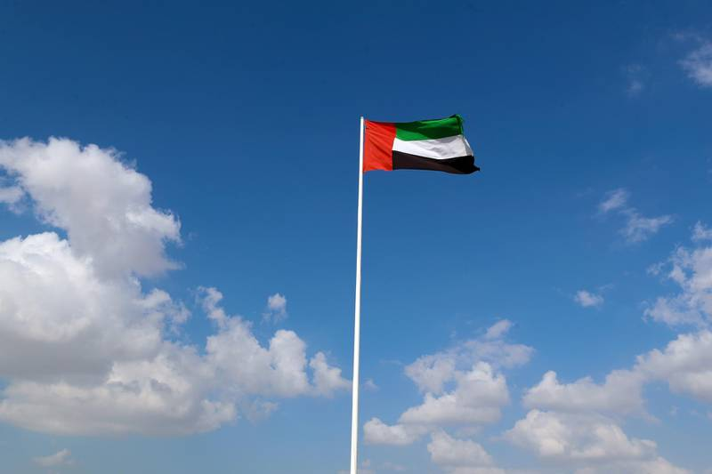 Dubai, United Arab Emirates - December 08, 2020: Weather. Strong winds blow the UAE flag up at Al Qudra cycle track. Tuesday, December 8th, 2020 in Dubai. Chris Whiteoak / The National