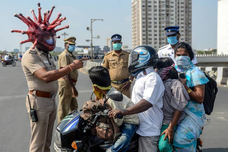 -- AFP PICTURES OF THE YEAR 2020 --  Police inspector Rajesh Babu (C) wearing coronavirus-themed helmet speaks to a family on a motorbike at a checkpoint during a government-imposed nationwide lockdown as a preventive measure against the COVID-19 coronavirus in Chennai on March 28, 2020. - One minute they're dancing in the street in comical coronavirus helmets, the next they're seen beating people for flouting a nationwide lockdown -- Indian police have played good cop, bad cop in a bid to halt the spread of coronavirus. The streets of India's cities have been largely deserted for more than a week of the government's 21-day lockdown -- no mean feat in a country of 1.3 billion people famed for their flexible attitude towards authority. (Photo by Arun SANKAR / AFP)
