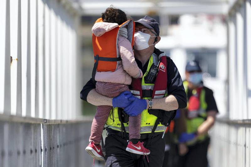 DOVER, ENGLAND - JUNE 09: Border Force officials hold a young girl that arrived with other migrants after being picked up in a dinghy in the English Channel on June 09, 2021 in Dover, England. More than 500 migrants arrived in the final week of May, according to the UK Home Office, adding that 3,600 people had been stopped from crossing the channel by French authorities. (Photo by Dan Kitwood/Getty Images) (Photo by Dan Kitwood/Getty Images)