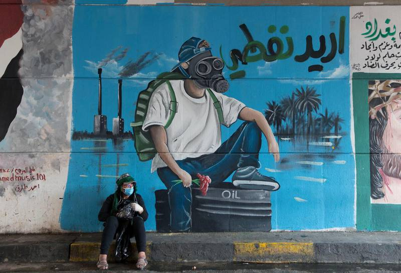"""FILE - In this Dec. 8, 2019 file photo, a protester rests by a mural with Arabic that reads, """"I want my oil,"""" in Baghdad, Iraq. The historic crash in oil prices in the wake of the novel coronavirus pandemic is reverberating across the Middle East as crude-dependent countries scramble to offset losses from a key source of state revenue. Iraq faces the most dire situation, and officials are trying to find ways to cut spending. Iraq saw massive protests the past months by a populace angry over the weak economy and rampant corruption -- and the turmoil could erupt again. (AP Photo/Nasser Nasser, File)"""