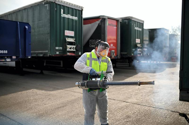 Business owner Chris Johnson uses a thermal fogger to disinfect trucks at a haulage firm in Barnsley,  south Yorkshire on April 22, 2020, during the nationwide lockdown due to the novel coronavirus COVID-19 pandemic. - Oxford University is launching a human trial of a potential coronavirus vaccine, with the daunting aim of making a succesful jab available to the public later this year. (Photo by Oli SCARFF / AFP)