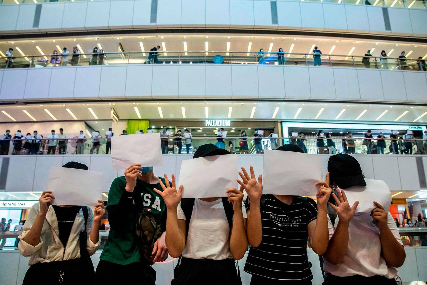 TOPSHOT - Protesters hold up blank papers during a demonstration in a mall in Hong Kong on July 6, 2020, in response to a new national security law introduced in the city which makes political views, slogans and signs advocating Hong Kong's independence or liberation illegal. Hong Kongers are finding creative ways to voice dissent after Beijing blanketed the city in a new security law and police began making arrests for people displaying now forbidden political slogans. / AFP / ISAAC LAWRENCE
