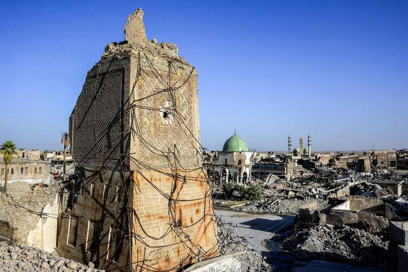 """TOPSHOT - A picture taken on July 9, 2018 shows a view of the base of the destroyed """"Al-Hadba"""" leaning minaret, with the dome of the destroyed Al-Nuri Mosque seen behind in the Old City of Mosul, a year after the city was retaken by the Iraqi government forces. Iraqi forces announced the """"liberation"""" of the country's second city on July 10, 2017, after a bloody nine-month offencive to end the Islamic State (IS) group's three-year rule there. Scores of people are still displaced in and around Mosul as the city lies in ruins, one year after it was retaken from IS.  / AFP / Zaid AL-OBEIDI"""