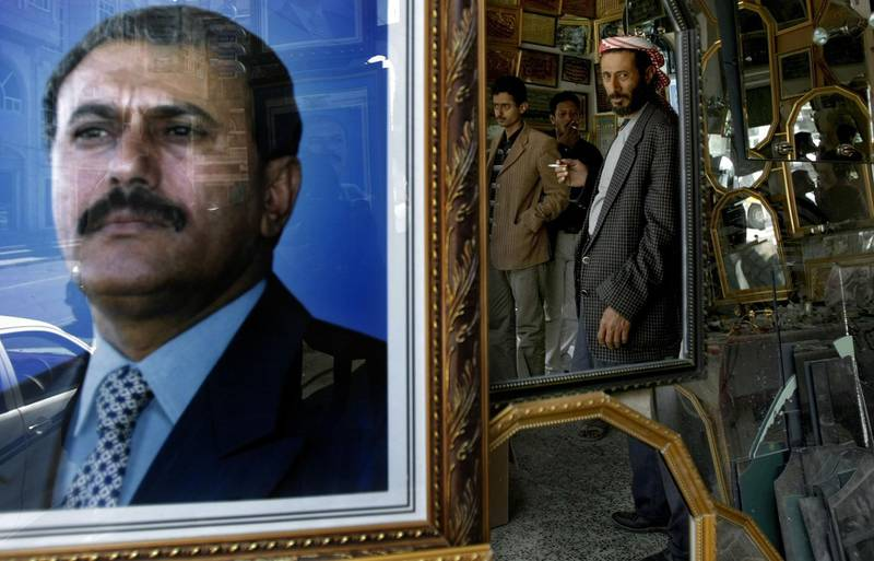 (FILES) This file photo taken on January 24, 2010 shows the reflection of Yemenis in a mirror next to a picture of Yemeni ex-president Ali Abdullah Saleh in Sanaa. Yemen's ex-president Ali Abdullah Saleh, slain by his former rebel allies died aged 75 on December 4, 2017.   / AFP PHOTO / MARWAN NAAMANI