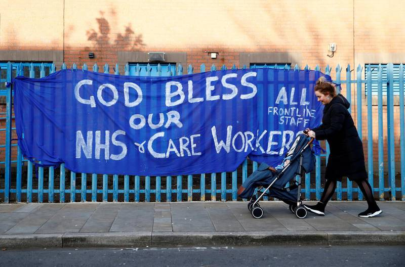 A woman passes with a stroller a banner showing support for the NHS, as the spread of the coronavirus disease (COVID-19) continues, Belfast, Northern Ireland, April 6, 2020. REUTERS/Jason Cairnduff