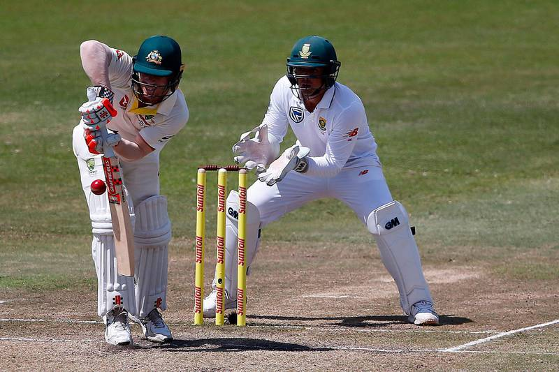 """(FILES) In this file photograph taken on March 3, 2018, Australian batsman David Warner (L) is watched by South African wicketkeeper Quinton de Kock as he plays a shot on the third day of the first Test cricket match between South Africa and Australia at The Kingsmead Stadium in Durban. Australian coach Darren Lehmann expects the coaches and captains of both teams to """"chat"""" before the second Test against South Africa starting in Port Elizabeth on March 9, 2018, after a bad-tempered start to the series. Lehmann was talking to Australian journalists after an acrimonious ending to the first Test in Durban after leaked closed-circuit television footage showed a confrontation between Australian vice-captain David Warner and South Africa's Quinton de Kock.  / AFP PHOTO / MARCO LONGARI"""