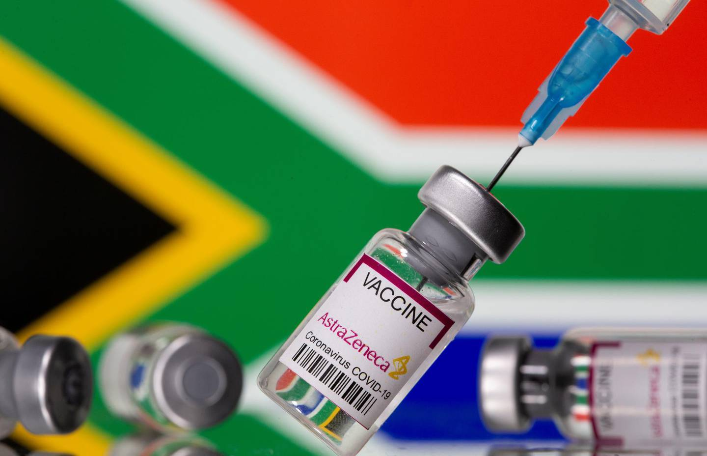 """Vials labelled """"Astra Zeneca COVID-19 Coronavirus Vaccine"""" and a syringe are seen in front of a displayed South Africa flag, in this illustration photo taken March 14, 2021. REUTERS/Dado Ruvic/Illustration"""