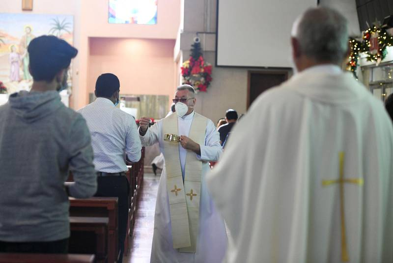 Abu Dhabi, United Arab Emirates - The sacramental bread for communion is handed out to the worshippers during Christmas mass, at St. JosephÕs Cathedral, Mushrif. Khushnum Bhandari for The National