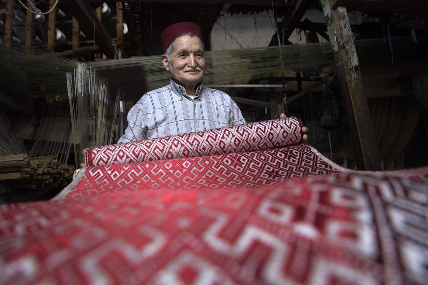 Abdelkader Ouazzani, the last of Morocco's brocade master weavers, displays tapestry at his workshop in the old city of Fes on April 10, 2019. His skillfull hands intricately create shimmering silk fabrics, enhanced with gold or silver thread, for bridal jewellery, designer creations or high-end furnishings. / AFP / FADEL SENNA