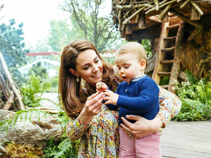 In this image made available on Sunday May 19, 2019 by Kensington Palace, Britain's Kate, Duchess of Cambridge and her son Prince Louis play in the Adam White and Andree Davies co-designed garden ahead of the RHS Chelsea Flower Show in London. (Matt Porteous/Kensington Palace via AP)