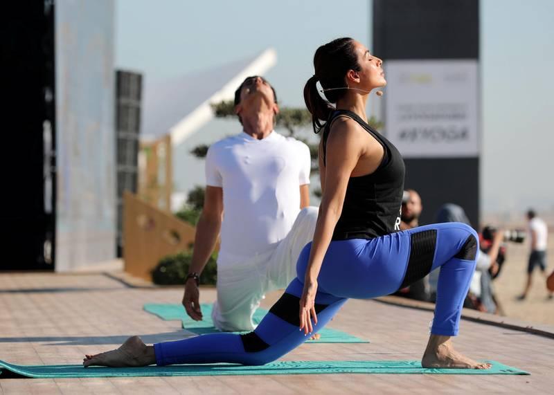 Dubai, United Arab Emirates - March 16th, 2018: Yogi Cameron (L). A mass yoga session hosted by Bollywood actress Malaika Arora as part of X Yoga Dubai. Friday, March 16th, 2018. Kite Beach, Dubai. Chris Whiteoak / The National