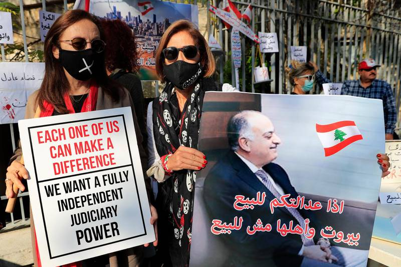 """A Lebanese activists holds a placard showing a portrait of Lebanese judge Fadi Sawan who is in charge of the investigation of the August explosion in Beirut, with Arabic that reads: """"if your justice is for sale, Beirut and its people not for sale,"""" during a protest outside the justice palace, in Beirut, Lebanon, Thursday, Dec. 3, 2020. The blast was one of the largest non-nuclear explosions in history and six months later, political and confessional rivalries have undermined the probe into the Beirut port explosion and brought it to a virtual halt, mirroring the same rivalries that have thwarted past attempts to investigate political crimes throughout Lebanon's history. (AP Photo/Hussein Malla)"""