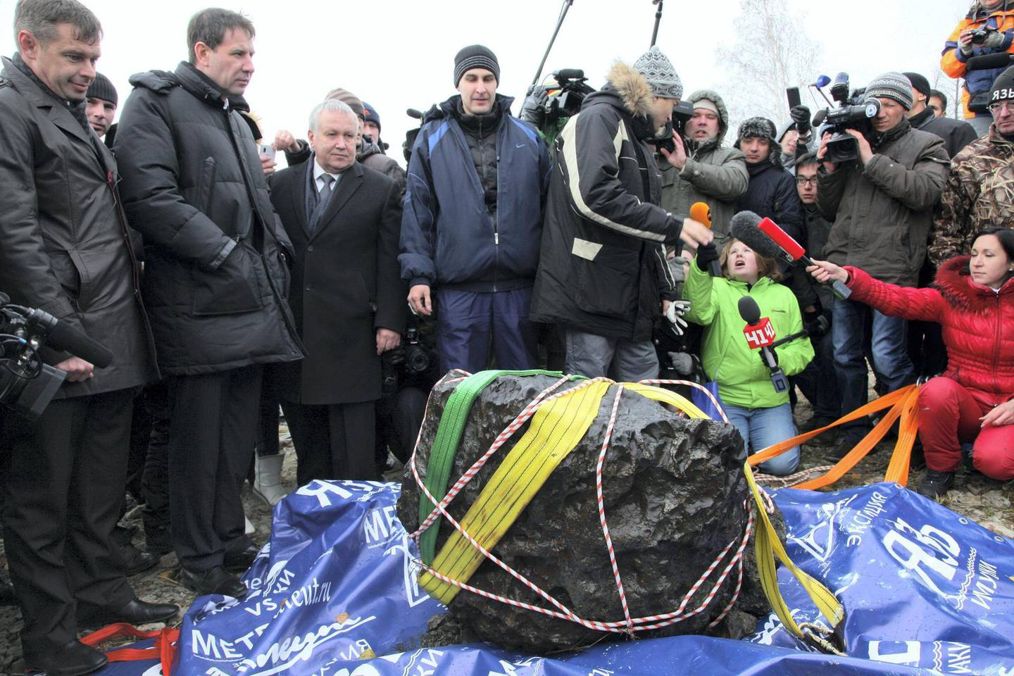 People look at what scientists believe to be a chunk of the Chelyabinsk meteor, recovered from Chebarkul Lake near Chelyabinsk, about 1500 kilometers (930 miles) east of Moscow,  Russia, Wednesday, Oct. 16, 2013. Scientists on Wednesday recovered what could be the largest part of this meteor from Chebarkul Lake outside the city. They weighed it using a giant steelyard balance, which displayed 570 kilograms (1,256 pounds) before it broke. (AP Photo/Alexander Firsov)