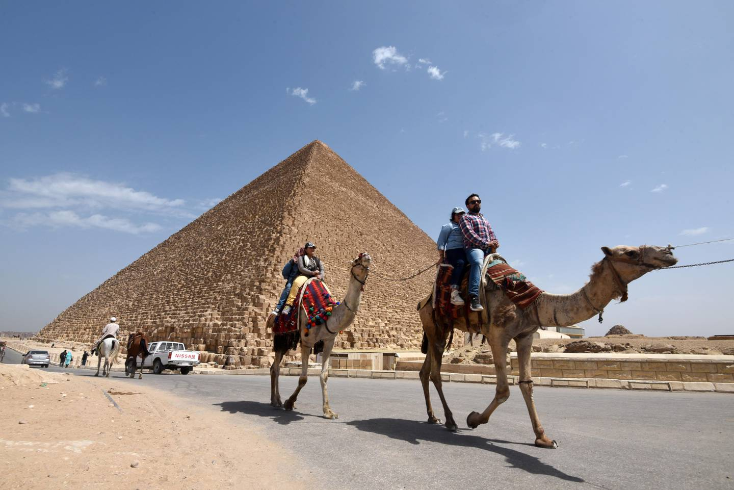 Tourists on camels ride past a pyramid at Cairo's northern Giza province, on March 29, 2017. / AFP PHOTO / MOHAMED EL-SHAHED