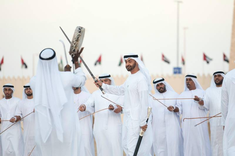 AL WATHBA, ABU DHABI, UNITED ARAB EMIRATES - December 3, 2018: HH Sheikh Mohamed bin Zayed Al Nahyan, Crown Prince of Abu Dhabi and Deputy Supreme Commander of the UAE Armed Forces (C), dances during the Sheikh Zayed Heritage Festival. ( Ryan Carter / Ministry of Presidential Affairs ) ---