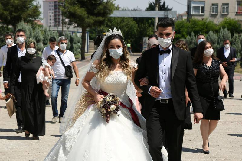 FILE PHOTO: Bride Pelsin Akkoyun and groom Nizamettin Bingol, wearing protective face masks, walk following their civil wedding ceremony, amid the spread of the coronavirus disease (COVID-19), in Diyarbakir, Turkey, July 2, 2020. Turkey reopened its wedding halls in one of the final steps of reopening from the shutdown due to the coronavirus disease (COVID-19). REUTERS/Sertac Kayar/File Photo