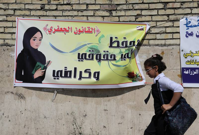 """In this Thursday, March 13, 2014 photo, a schoolgirl passes by a banner for the Jaafari Personal Status Law in Baghdad, Iraq. The Arabic on the banner reads, """"the Jaafari Personal Status Law saves my rights and my dignity."""" A contentious civil status draft law for Iraqi Shiite community that allows child marriage and restricts women's rights has stirred up a row among many Iraqis who see it as a setback for child and women rights, threatening to add more divisions and woos to the society that is already in fragments. (AP Photo/Karim Kadim)"""