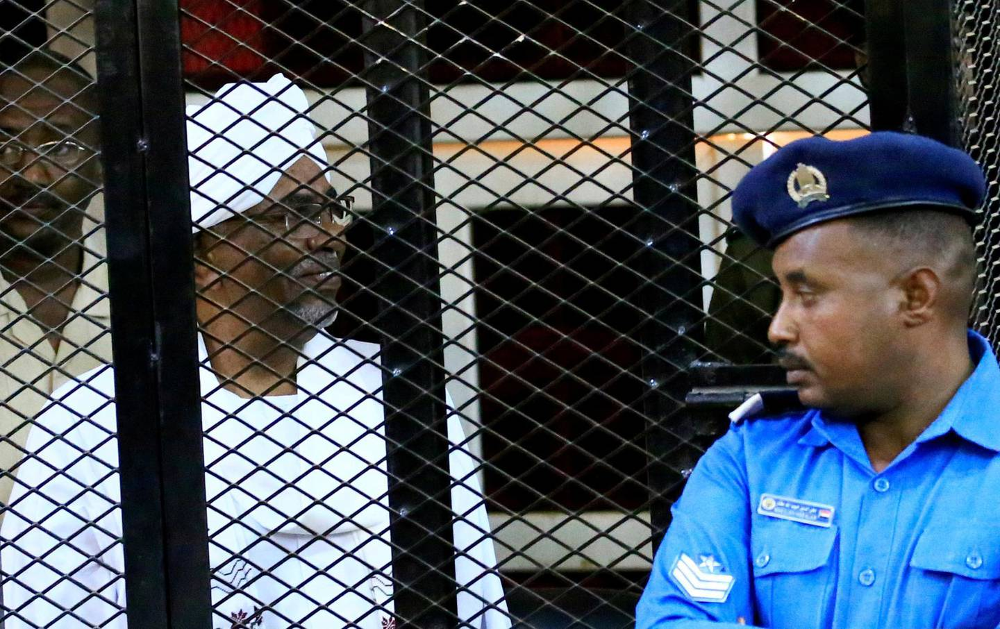 FILE PHOTO: Sudan's former president Omar Hassan al-Bashir sits inside a cage during the hearing of the verdict that convicted him of corruption charges in a court in Khartoum, Sudan, December 14, 2019. REUTERS/Mohamed Nureldin Abdallah/File Photo