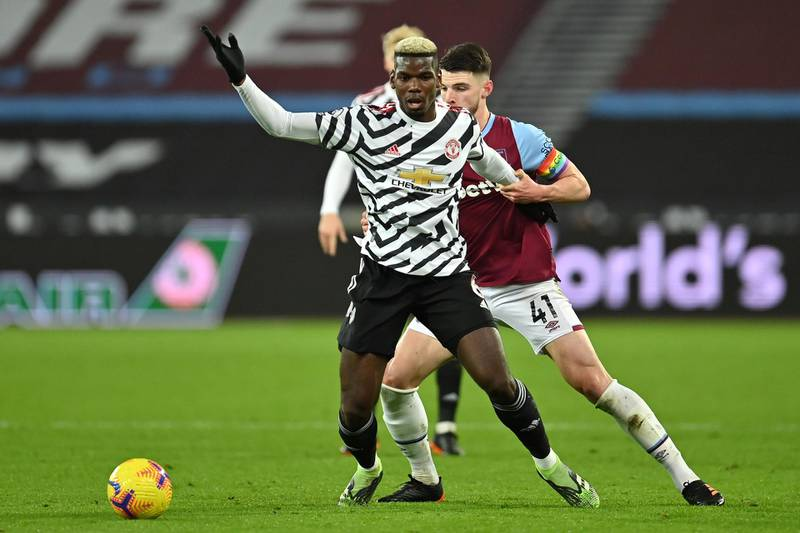 LONDON, ENGLAND - DECEMBER 05: Paul Pogba of Manchester United holds off Declan Rice of West Ham United during the Premier League match between West Ham United and Manchester United at London Stadium on December 05, 2020 in London, England. A limited number of fans are welcomed back to stadiums to watch elite football across England. This was following easing of restrictions on spectators in tiers one and two areas only. (Photo by Justin Setterfield/Getty Images)