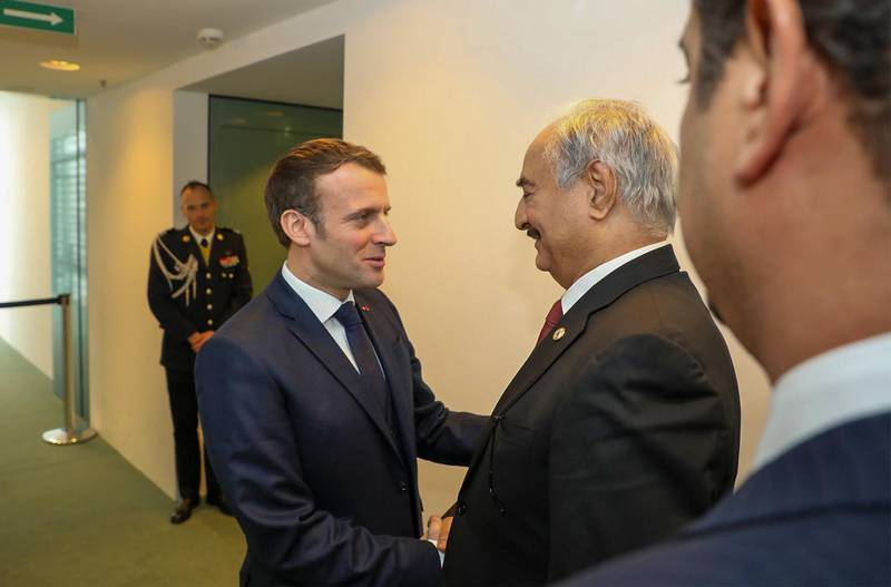 """This image grab taken from a video obtained from the Libyan strongman Khalifa Haftar's self-proclaimed Libyan National Army War Information Division's Facebook page on January 16, 2020, shows Haftar (2nd-R) greeting with French President Emmanuel Macron (C) in the German capital Berlin. World leaders made a fresh push for peace in Libya at a summit in Berlin, in a desperate bid to stop the conflict-wracked nation from turning into a """"second Syria"""". The presidents of Russia, Turkey and France joined other global chiefs at the talks hosted by Chancellor Angela Merkel and held under the auspices of the United Nations. - RESTRICTED TO EDITORIAL USE - MANDATORY CREDIT """"AFP PHOTO / LNA WAR INFORMATION DIVISION"""" - NO MARKETING NO ADVERTISING CAMPAIGNS - DISTRIBUTED AS A SERVICE TO CLIENTS  / AFP / LNA War Information Division / - / RESTRICTED TO EDITORIAL USE - MANDATORY CREDIT """"AFP PHOTO / LNA WAR INFORMATION DIVISION"""" - NO MARKETING NO ADVERTISING CAMPAIGNS - DISTRIBUTED AS A SERVICE TO CLIENTS"""