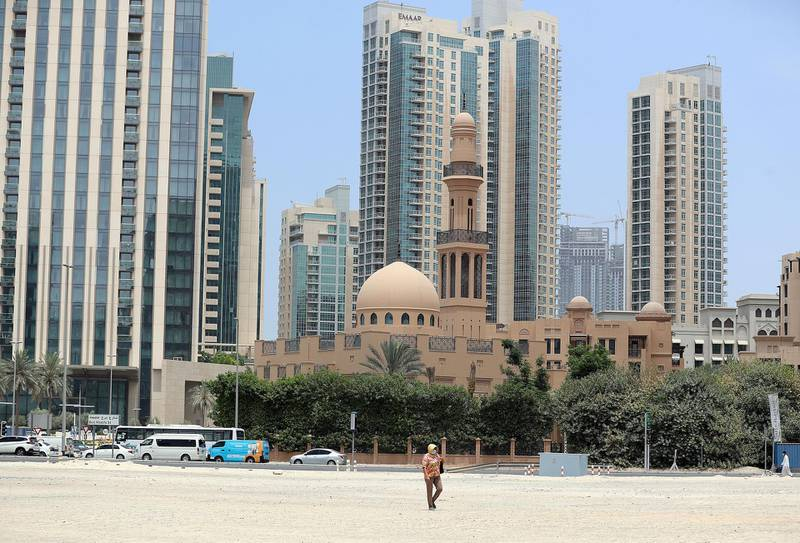 Street photography. A women walks through the sand in Downtown Dubai on April 29th, 2021. Chris Whiteoak / The National.  Reporter: N/A for News