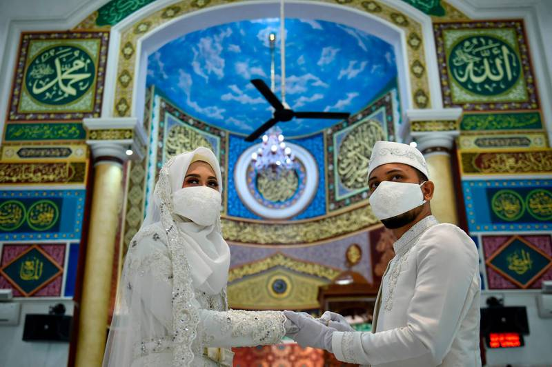 A couple wearing face masks amid the COVID-19 coronavirus attends to their wedding ceremony at a mosque in Banda Aceh on June 3, 2020. / AFP / CHAIDEER MAHYUDDIN