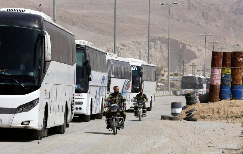 Syrian regime forces drive motorbikes past buses waiting at the entrance of Harasta in Eastern Ghouta, on the outskirts of Damascus, on March 22, 2018, after a deal was struck with the rebels in the area to evacuate the town. The deal to evacuate mainly members of the hardline Islamist rebel group Ahrar al-Sham and their families was announced on March 21 and brokered by regime ally Russia.  / AFP PHOTO / Louai Beshara