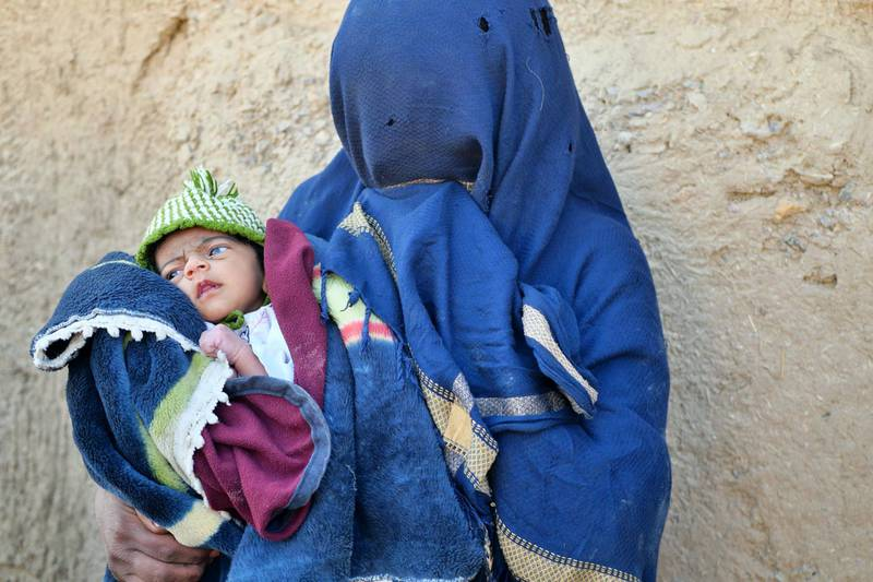 Pictured: Amina, 30, cradles her weeks-old baby boy in the grounds of the dilapidated house her and her family have fled to following the conflict in her village of Pashmol, Kandahar. Photo by Charlie Faulkner January 2021