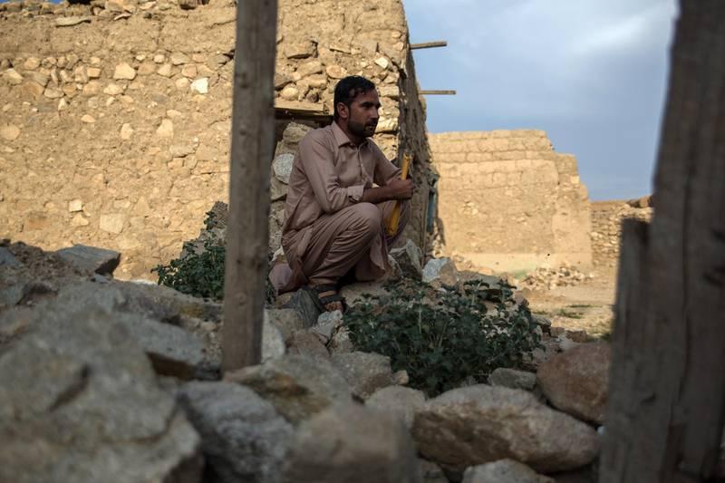 Nakibullah Sahir, 29, sits in the ruins of his house in Pekha village, Achin District.