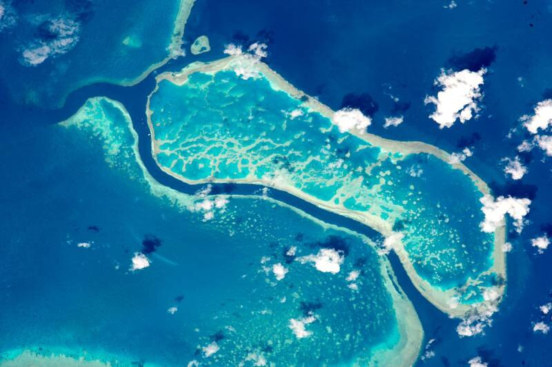epa05346453 A handout picture made available by NASA on 05 June 2016 shows an image taken by an astronaut aboard the International Space Station (ISS) using powerful lens to photograph three reefs of Australia's Great Barrier Reef, seen from space, 15 October 2015. The photo area spans about 15km of the 2,300km reef system. Reefs are easy to spot from space as the iridescent blues of shallow lagoons contrast sharply with the dark blues of deep water. The Great Barrier Reef is the largest reef system on Earth, with more than 3,000 separate reefs and coral cays. It is also one of the most complex natural ecosystems, with 600 types of corals and thousands of animal species from tiny planktons to whales.  EPA/NASA  HANDOUT EDITORIAL USE ONLY *** Local Caption *** 52804080