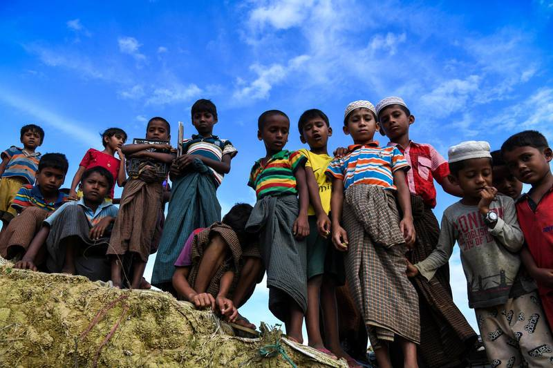 Rohingya refugee children look on at the Kutupalong camp in Ukhia near Cox's Bazar on August 12, 2018. - Nearly 700,000 Rohingya fled Myanmar's Rakhine state last year to escape a violent military crackdown. The United Nations has described the army purge against the persecuted minority as ethnic cleansing, and thousands of Rohingya Muslims were believed to have been slaughtered in the pogrom that began last August. (Photo by CHANDAN KHANNA / AFP)