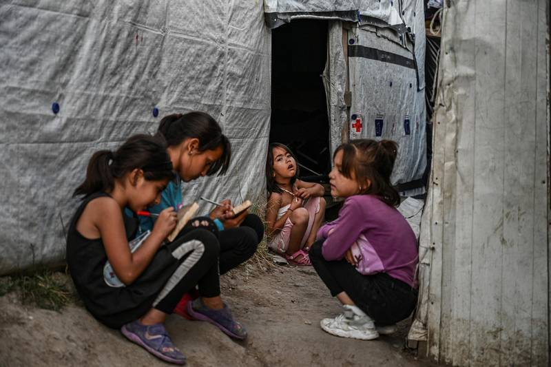 Childs are pictured in a improvised tents camp near the refugee camp of Moria in the island of Lesbos on June 21, 2020. - Greece's announcement that it was extending the coronavirus lockdown at its migrant camps until July 5, cancelling plans to lift the measures on June 22, coincided with World Refugee Day on June 27, 2020. (Photo by ARIS MESSINIS / AFP)
