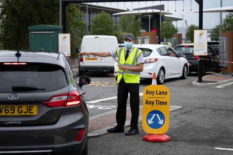 SWANSEA, UNITED KINGDOM - JUNE 03: A worker at a McDonald's restaurant wears a surgical face mask as he ushers cars into a drive-through lane on June 03, 2020 in Swansea, United Kingdom. The restaurant has reopened its doors for drive-through customers only. The Welsh government has further relaxed COVID-19 lockdown measures this week, allowing people from different households to meet up outside while maintaining social distancing. Schools have remained closed and those who have been advised to shield at home can go outside again but have been told to avoid shopping. (Photo by Matthew Horwood/Getty Images)
