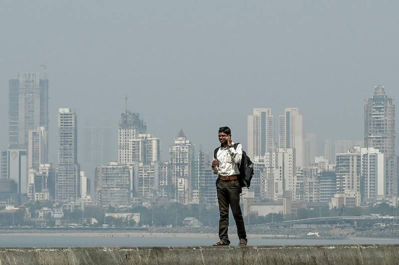 A man speaks on a mobile phone as he stands near the sea front overlooking the city skyline in Mumbai on February 18, 2020. / AFP / PUNIT PARANJPE