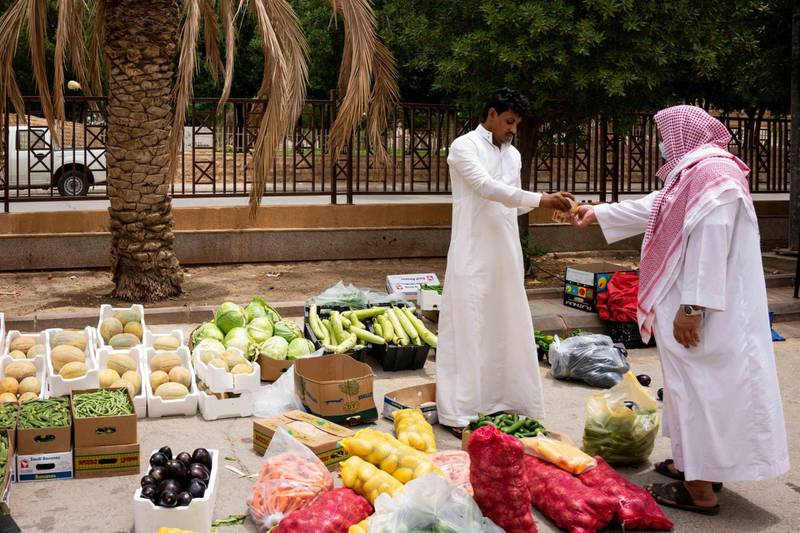 A street vendor sells fruit and vegetables on a roadside in Riyadh, Saudi Arabia, on Tuesday, May 19, 2020. Hit simultaneously by plunging crude prices and coronavirus shutdowns, the non-oil economy is expected to contract for the first time in over 30 years. Photographer: Tasneem Alsultan/Bloomberg