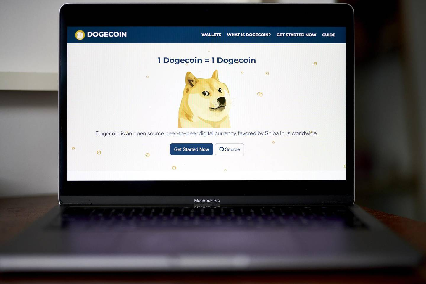 """The Dogecoin website on a laptop computer arranged in the Brooklyn borough of New York, U.S., on Friday, May 7, 2021. Dogecoin, a cryptocurrency conceived as a joke but now the world's fifth-most valuable,plunged from an all-time highafter its most famous cheerleader,Elon Musk, jokingly called it """"a hustle"""" on late-night TV. Photographer: Gabby Jones/Bloomberg"""