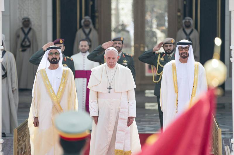 ABU DHABI, UNITED ARAB EMIRATES - February 04, 2019: Day two of the UAE papal visit - (R L) HH Sheikh Mohamed bin Zayed Al Nahyan, Crown Prince of Abu Dhabi and Deputy Supreme Commander of the UAE Armed Forces, His Holiness Pope Francis, Head of the Catholic Church and HH Sheikh Mohamed bin Rashid Al Maktoum, Vice-President, Prime Minister of the UAE, Ruler of Dubai and Minister of Defence, stand for a national anthem during a reception, at the Presidential Palace.  ( Rashed Al Mansoori / Ministry of Presidential Affairs ) ---