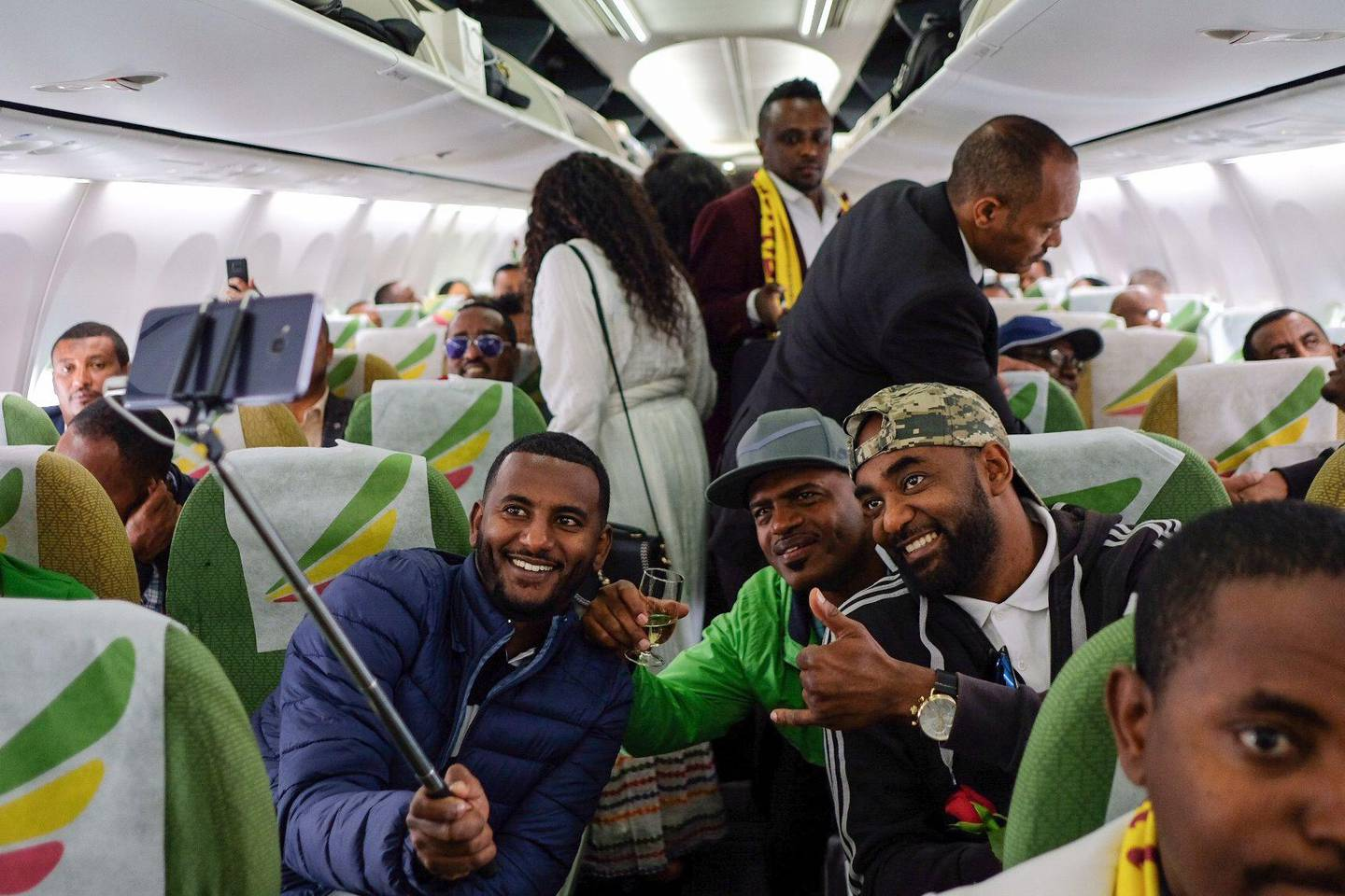 Passengers pose for a selfie picture inside an Ethiopian Airlines flight who departed from the Bole International Airport in Addis Ababa, Ethiopia, to Eritrea's capital Asmara on July 18, 2018.  The first commercial flight to Eritrea in two decades departed on July 18, 2018 from Addis Ababa after the two nations ended their bitter conflict in a whirlwind peace process.  / AFP / Maheder HAILESELASSIE TADESE