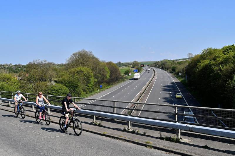 Cyclists ride bikes as the cross a bridge over empty carriageways of the M4 motorway below, near Swindon, western England, on April 11, 2020, as life in Britain continues over the Easter break, during the nationwide lockdown to combat the novel coronavirus pandemic. - Prime Minister Boris Johnson was able to walk in hospital on Friday some 24 hours after leaving intensive care treatment for COVID-19, as Britain recorded nearly 1,000 daily deaths from the virus for the first time. (Photo by JUSTIN TALLIS / AFP)